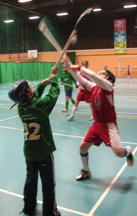 Edinburgh player competes for a throw-up ball in an indoor shinty tournament